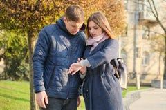 Junger Mann und Frau in der Stadt, Armbanduhr betrachtend, goldene Stunde, Frühlings-Saison stockbilder