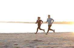 Junger Mann und Frau, die entlang die Ufergegend läuft Lizenzfreie Stockbilder