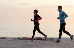 Junger Mann und Frau, die entlang die Ufergegend läuft Stockfotos