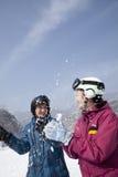 Junger Mann und Frau, die im Schnee in Ski Resort spielt Stockfotos