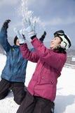 Junger Mann und Frau, die im Schnee in Ski Resort spielt Stockfotografie