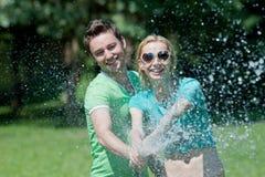 Junger Mann und Frau, die mit Wasserspray spielt Lizenzfreie Stockfotografie