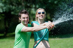 Junger Mann und Frau, die mit Wasserspray spielt Stockbild