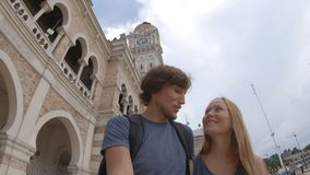 Junger Mann und Frau, die um Sultan Abdul Samad Building in Kuala Lumpur-vity, Malaysia geht stock video footage