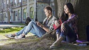 Junger Mann und Frau, die unter Baum, seiend beim ersten Treffen, Ungeschicklichkeit sitzt schüchtern lizenzfreies stockfoto