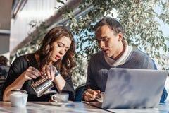 Junger Mann und Frau, die vor dem Laptop und dem trinkenden Tee arbeitet lizenzfreie stockbilder