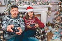 Junger Mann und Frau, die zusammen Spiele sitzt und spielt Sie Druckknöpfe auf Konsole Leute sorgen sich Sie spielen herein stockbild