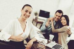 Junger Mann und Frau mit lächelndem Grundstücksmakler im Büro stockbilder