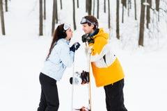 Junger Mann und Frau mit treir Snowboards Stockbilder