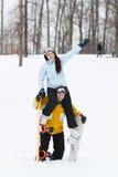 Junger Mann und Frau mit treir Snowboards stockfoto
