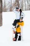Junger Mann und Frau mit treir Snowboards stockfotos