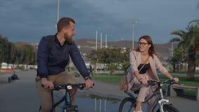 Junger Mann und Frau sind, reiten treffend und Fahrräder im Park in der Tageszeit stock video footage