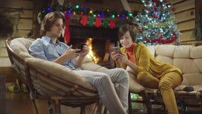 Junger Mann und Frau unter Verwendung der Smartphones und der Mannaktien seins mit Frau, Heilige Nacht stock video