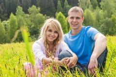 Junger Mann und Mädchen auf Wiese lizenzfreies stockfoto