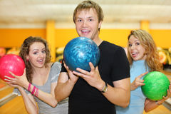 Junger Mann und Mädchen halten Kugeln im Bowlingspielklumpen an Stockfotos