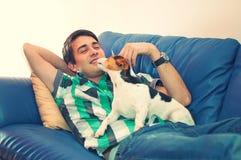 Junger Mann und sein Hund auf einer Couch lizenzfreie stockfotos