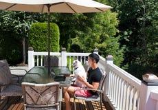 Junger Mann und sein Schoßhund, die vom Haus auf seinem Zedernausgangsde arbeitet lizenzfreies stockbild