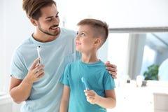 Junger Mann und sein Sohn mit Zahnbürsten im Badezimmer, Raum für Text lizenzfreie stockfotos