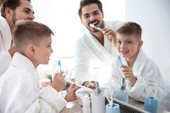 Junger Mann und sein Sohn mit Zahnbürsten nahe Spiegel im Badezimmer stockfotografie