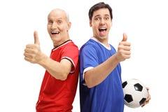 Junger Mann und Senior mit dem Fußball, der Daumen herauf Zeichen herstellt Lizenzfreie Stockfotos