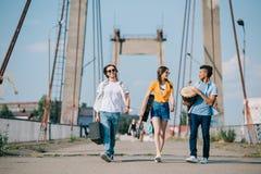 Junger Mann und weibliche Buskers, die Instrumente auf sonnigem tragen stockfotografie