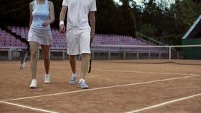 Junger Mann und weibliche Tennisspieler, die oben auf Gericht, nach Match, Abschluss gehen lizenzfreie stockfotografie