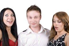 Junger Mann und zwei überraschten junge Frauen Stockfotografie