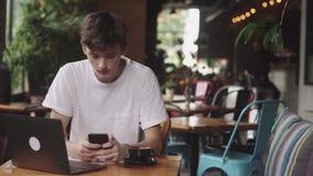 Junger Mann unter Verwendung der Kopfhörer mit Drähten zur Registrierung der Musik im Café, moderner Arbeitsplatz, der im Café si stock footage