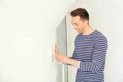 Junger Mann unter Verwendung des Sicherheitssystems zuhause lizenzfreie stockfotos
