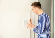 Junger Mann unter Verwendung des Sicherheitssystems zuhause lizenzfreie stockbilder