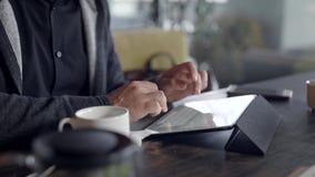 Junger Mann unter Verwendung des Tablet-Computers und trinkender Tee im Café stock video