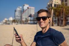 Junger Mann unter Verwendung des Telefons mit Kopfhörer auf dem Strand Stadtskyline im Hintergrund lizenzfreie stockfotografie