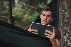 Junger Mann unter Verwendung einer Tablette auf einer H?ngematte stockbild