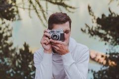 Junger Mann unter Verwendung einer Weinlesekamera vor einem Türkissee stockbilder