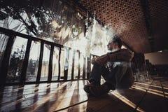 Junger Mann Vaping produziert Dampf auf Sonnenuntergangschattenbild lizenzfreies stockbild