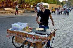 Junger Mann verkauft Lebensmittel Stockbild