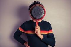 Junger Mann versteckende beind Bratpfanne Stockfotografie