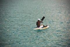 Junger Mann von den Seychellen auf einem Surfbrett im Ozean Lizenzfreie Stockfotografie