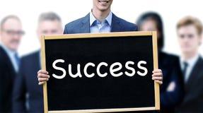 Junger Mann vor der Gruppe, die Zeichen mit Wort Erfolg hält stockfotografie