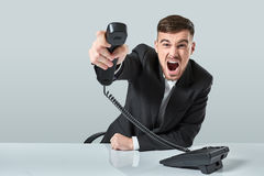 Junger Mann wählt die Telefonnummer beim Sitzen im Büro Lizenzfreie Stockfotografie