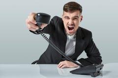 Junger Mann wählt die Telefonnummer beim Sitzen im Büro Stockbilder