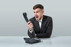 Junger Mann wählt die Telefonnummer beim Sitzen im Büro Lizenzfreies Stockbild