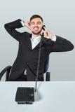 Junger Mann wählt die Telefonnummer beim Sitzen im Büro Lizenzfreies Stockfoto