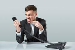 Junger Mann wählt die Telefonnummer beim Sitzen im Büro Lizenzfreie Stockfotos