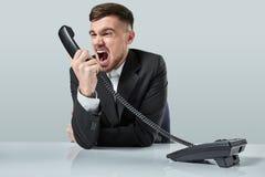 Junger Mann wählt die Telefonnummer beim Sitzen im Büro Stockbild