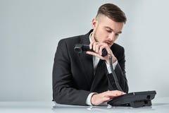 Junger Mann wählt die Telefonnummer beim Sitzen im Büro Stockfotografie