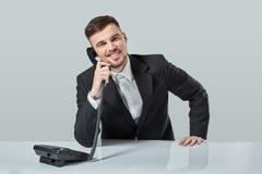 Junger Mann wählt die Telefonnummer beim Sitzen im Büro Lizenzfreie Stockbilder