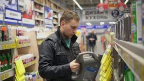 Junger Mann wählt Motorenöl für Auto an der Reparaturtankstelle oder im Supermarkt Verschiedene Kanister auf Regalen stock video