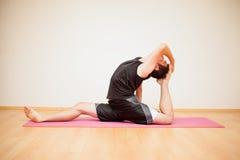 Junger Mann während der Yogapraxis Stockfotografie