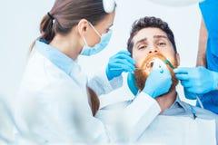 Junger Mann während eines schmerzlosen Mundverfahrens im zahnmedizinischen Büro Stockfotografie